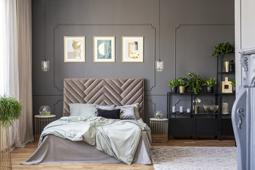Dark bedroom interior with a comfy double bed, paintings and black shelf and wall molding
