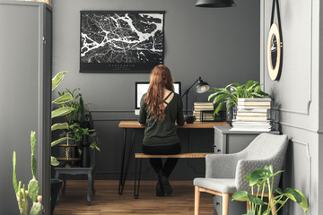Woman working at desk with lamp in grey workspace interior with poster and armchair. Real photo