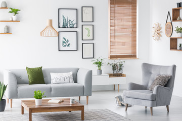 Real photo of a cozy living room interior with a sofa, green pillow, armchair, art gallery and wooden coffee table