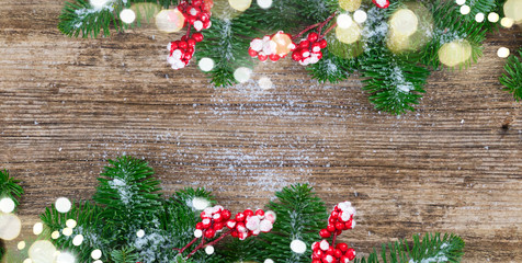 red and white christmas - twig with red berries and green evergreen tree on wooden background banner with copy space