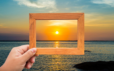 hand hold photo frame and focus  through the sunrise on background. keep the wonderful memory is concept.