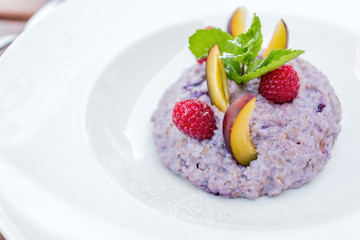 Oatmeal porridge with blueberries, raspberries and peach.
