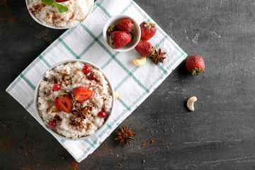 Bowls with delicious rice pudding, anise and berries on dark table