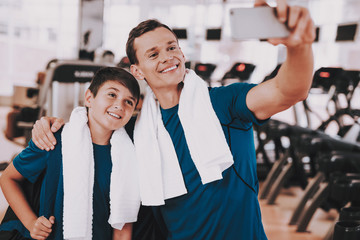 Young Father and Son Taking Selfie near Treadmills