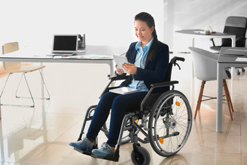 Asian woman in wheelchair working with tablet PC in office