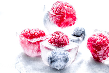 Ice cubes with frozen berries on white background