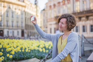 A tourist woman is walking around Prague on a sunny day.