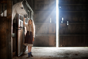girl palming horse in the stable
