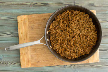 Kitchen skillet filled with cooked ground beef