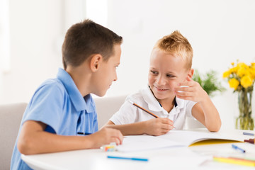 Two smiling little boys drawing in the notebook and talking to each other.