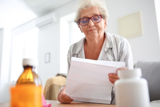 Senior woman reading instruction before taking medicines at home