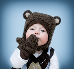little boy in a bear suit sends a kiss