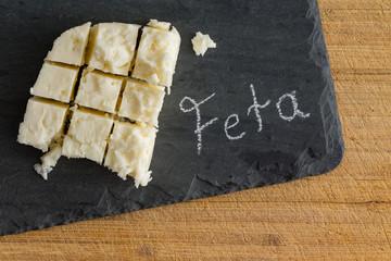 Diced slab of feta cheese on a slate board