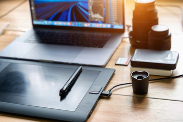 Drawing tablet and laptop computer, harddisk, memory card, camera lens on table. Photographer concept.