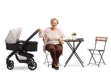 Elderly woman with a baby stroller sitting at a coffee table