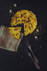 Overhead view of pumpkin pie on black background
