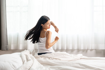 Woman waking up, stretching in bed.