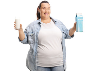 Overweight woman with a glass of milk and a milk carton