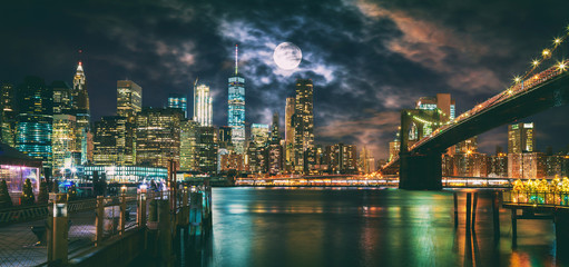 New York City Brooklyn Bridge and Manhattan skyline illuminated at night with full moon overhead.