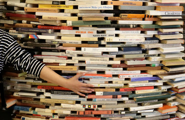 A woman touches books piled up at the entrance of Municipal Library of Prague in Prague