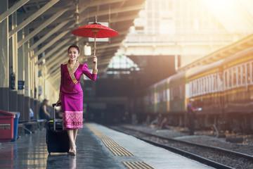 Traveler girl walking and waits train on railway platform