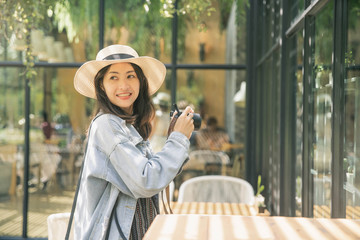 Happy girl making photo with camera on travel trip. Woman Taking Photos On Camera . Smiling woman in trendy hat making photo outdoors, traveling to the  City.
