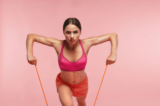 Workout. Woman Training With Resistance Bands On Pink Background