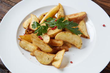 Homemade roasted potato with parsley on rustic background.