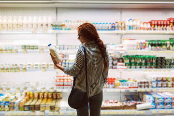 Pretty girl in eyeglasses and striped shirt choosing milk in dairy department in supermarket
