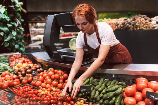 Young seller in apron standing behind counter with vegetables thoughtfully working in supermarket