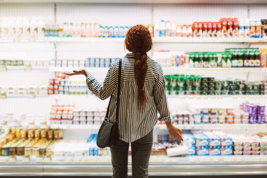 Young woman in striped shirt from back trying to choose dairy products in modern supermarket