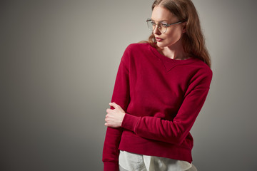 beautiful woman in stylish outfit and eyeglasses looking away isolated on grey