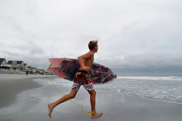 Surfer Ryan Largin, 12, of Garden City Beach, runs to the surf ahead of the arrival of Hurricane Florence in Garden City Beach
