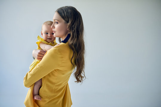side view of stylish woman carrying adorable baby girl isolated on grey