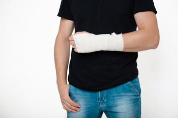 Young handsome guy in a black T-shirt with bandaged hand on a white background. A man with a hand in a bandage bandage.