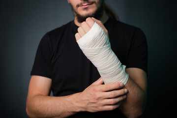 A young handsome guy in a black T-shirt with a bandaged hand on a gray background. A man with a hand in a bandage bandage.