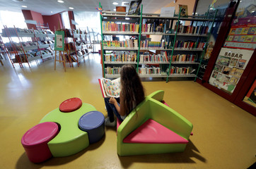 "A young girl reads a comic book at the ""Louis Nucera"" library in Nice"