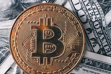 Gold Bit Coin BTC coins  on bills dollars. Worldwide virtual internet cryptocurrency and digital payment system. Digital coin money crypto currency  in digital cyberspace