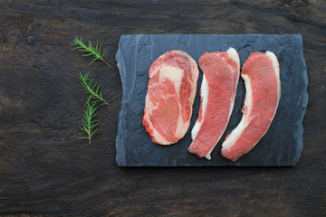 Top view of Raw beef steak with rosemary on wooden dark background, food meat or barbecue