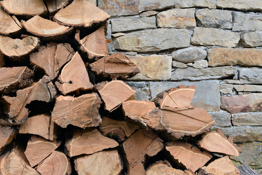 Pile of firewood logs by stone wall - detail