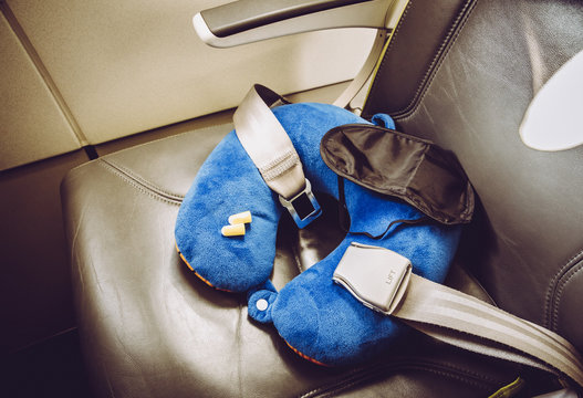 Blue soft traveling pillow, noise removing ear plugs and sleeping mask, in plane cabin on passenger seat, comfortable cozy traveling concept, composition.