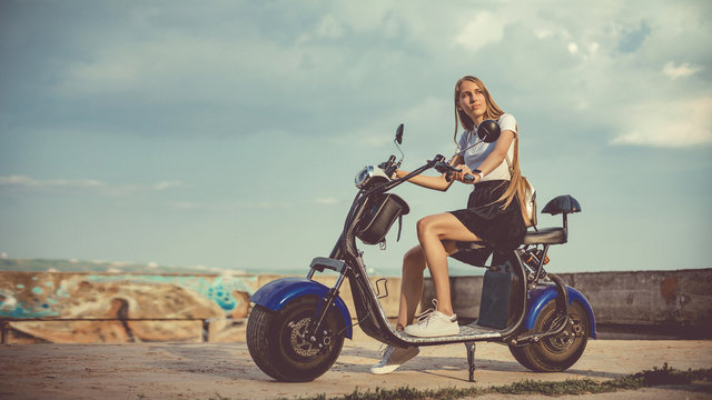 Young Woman Riding Electro Scooter On Country Road