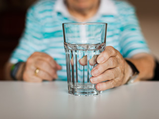 Hand of senior lady holding a glass of water on table