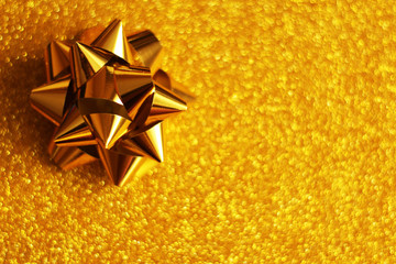 Golden glitter background, golden present ribbon, concept of gift for Christmas, birthday, celebrations, wedding, etc.