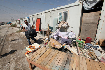 A displaced Christian holds TV at Ankawa refugee camp in Erbil