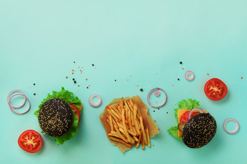 Black burger, french fries potatoes, tomatoes, cheese, onion, cucumber and lettuce on blue background. Top view. Fast food banner with copy space. Take away meal. Unhealthy diet concept