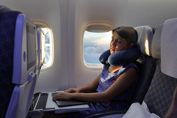 Young woman sleeps in airplane during the flight