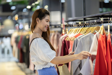 Beautiful Attractive Asian young woman choose cloth hang on shelf in Clothes store feeling so happiness and enjoy in shopping mall,Selective focus,Fashion and Shopping concept