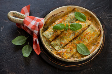 Baking pan with freshly cooked spinach and cheese cannelloni topped with green basil leaves, dark brown stone background