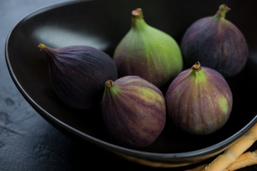 Close-up of ripe fig fruits served in a black bowl, selective focus, studio shot